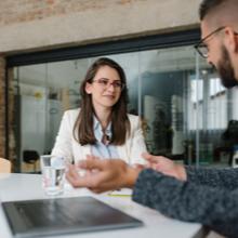 Jeune femme qui passe un entretien d'embauche face à un recruteur dans un bureau avec un ordinateur portable